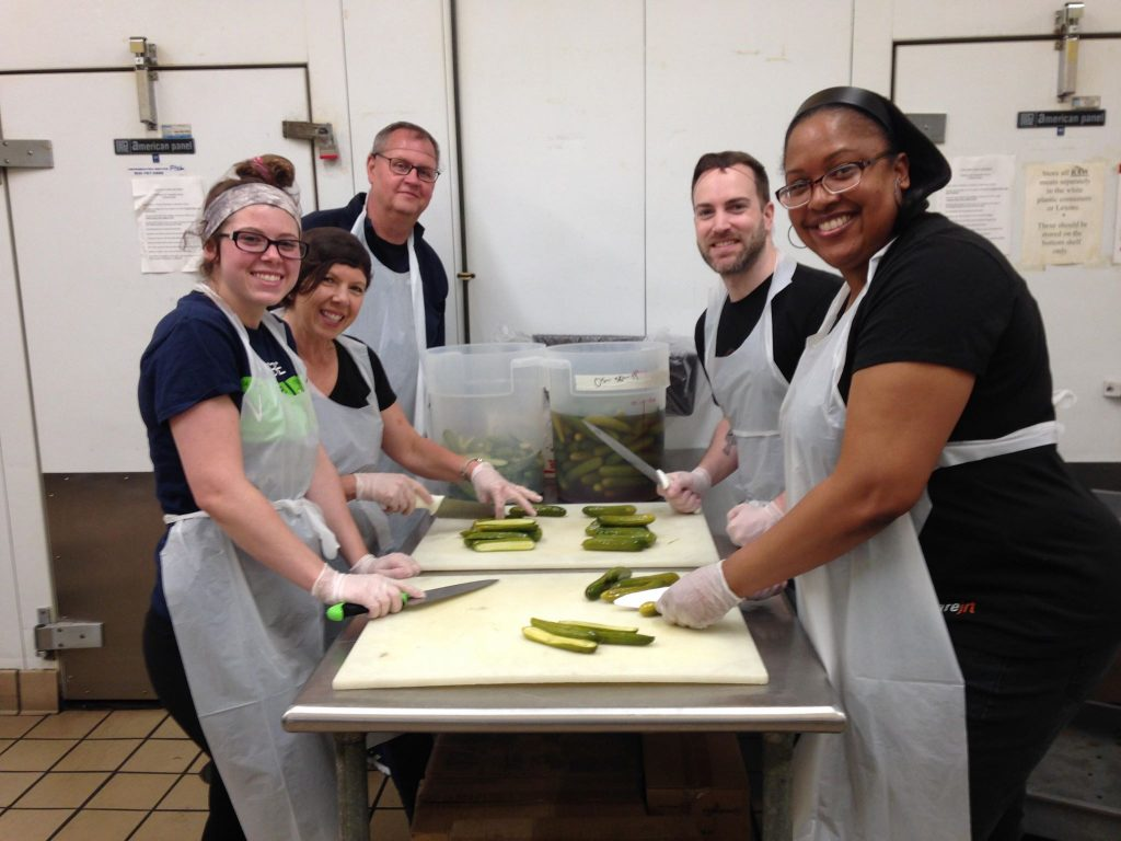 a group of people cutting pickles
