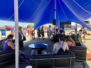 people lounging on couches under a large tent