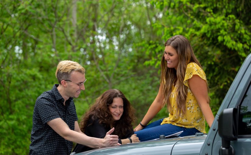 Two women and one man with a Jeep Wrangler