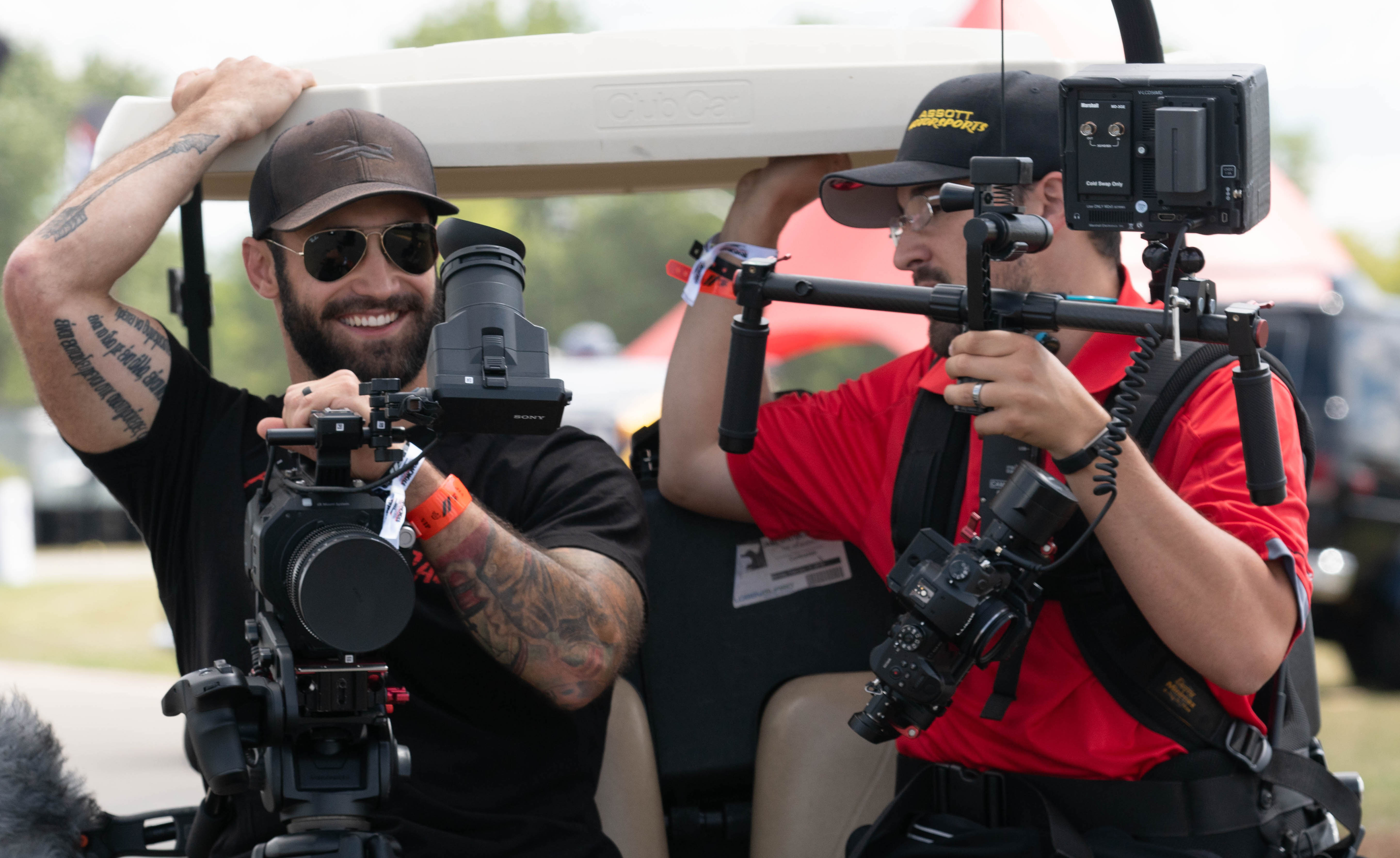 Two men on a golf cart with video equipment