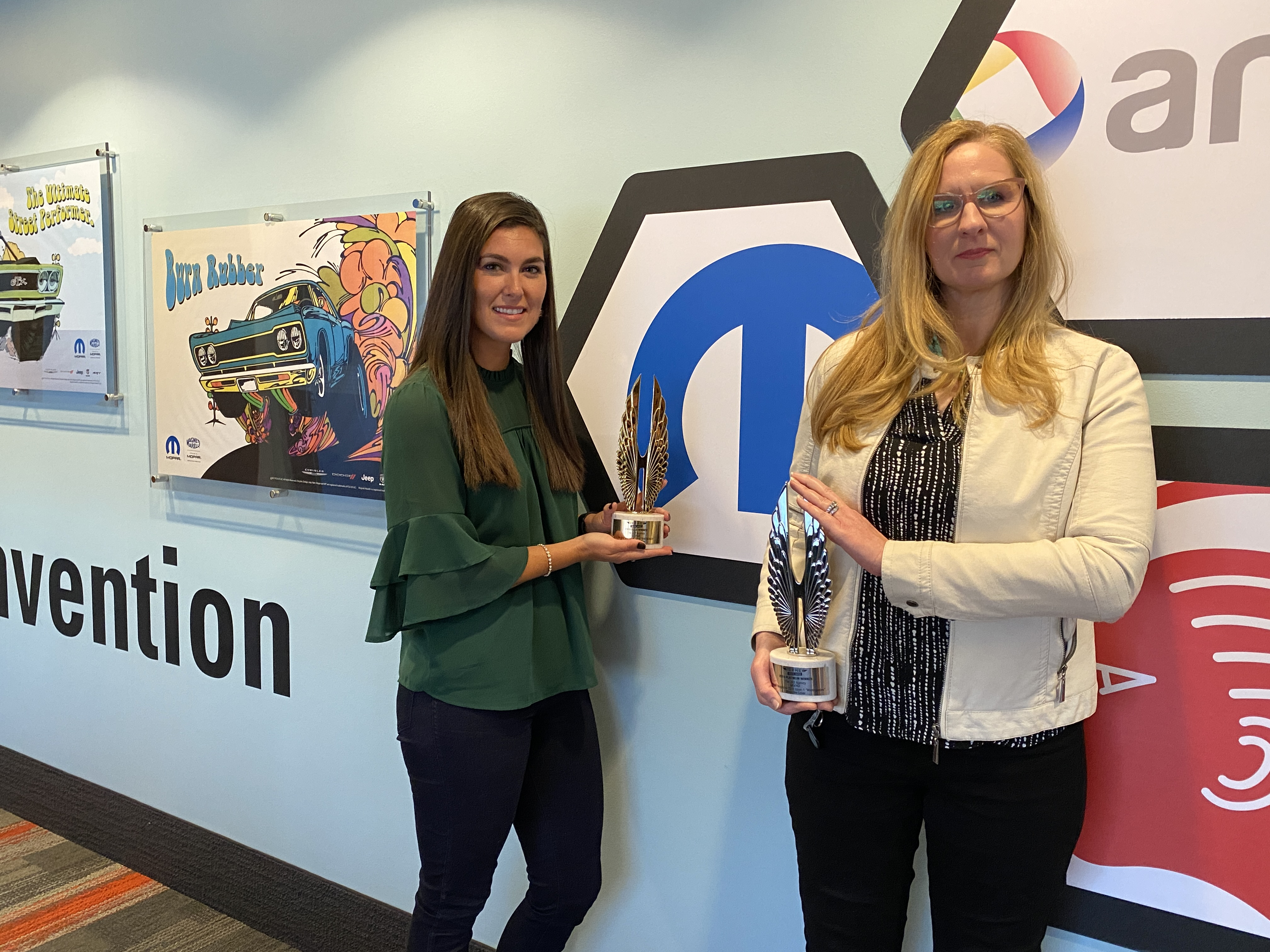 Two women holding awards