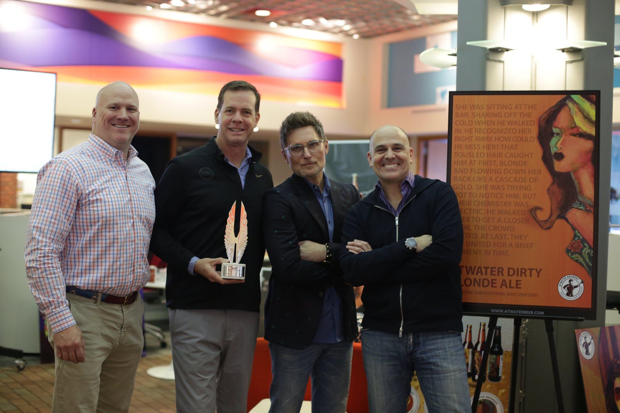 Four men holding an awards